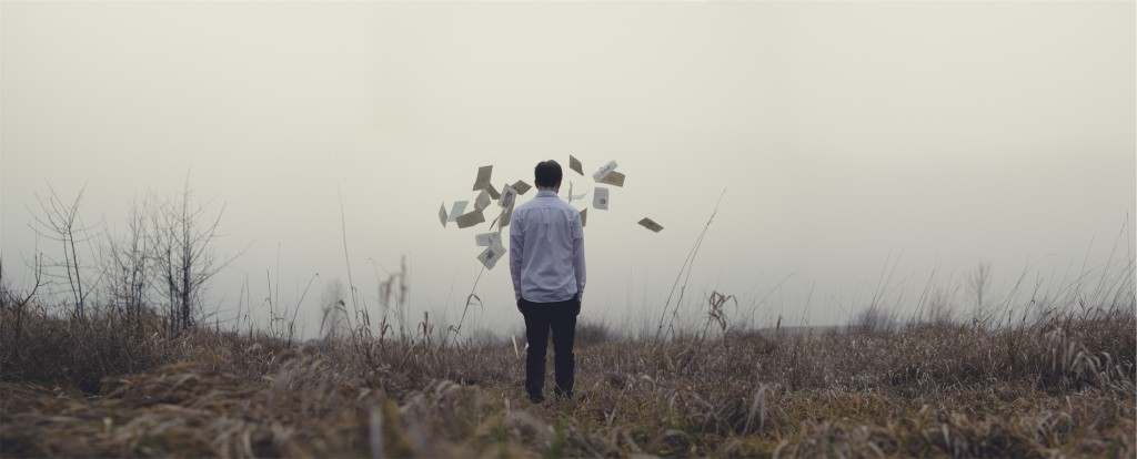 Guy looking at flying papers